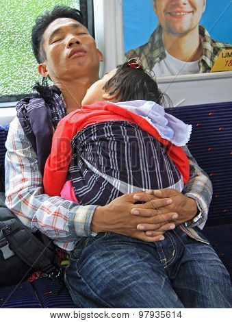 father with baby daughter in carrage of commuter train