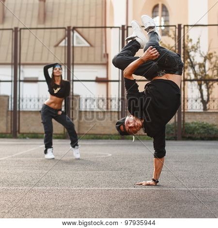 The Young Dancer Standing On His Hand. Dancing Hip Hop With A Beautiful Girl.