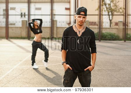 Portrait Of Handsome Hip Hop Man In Stylish Black Clothes. In The Background A Beautiful Girl