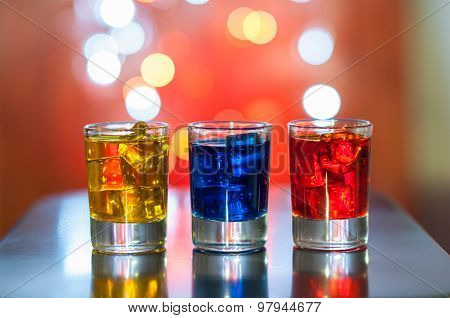 Bright alcohol drinks or berries cocktail in different colours, glasses tumbler on light bokeh backf