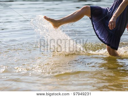 Girl Splashing Water In Lake By Her Leg