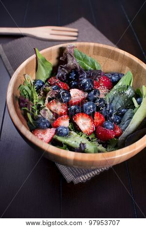 Healthy fresh salad on wooden bowl with berries and spinach