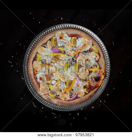 Fresh baked home made veggie pizza with figs and feta cheese over black background
