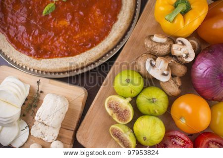Rustic home made pizza on wooden table with fresh ingredients and cheese