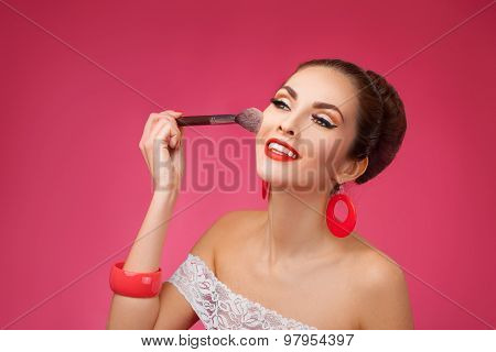 Smiling Woman with makeup brush. She is standing against a pink background.