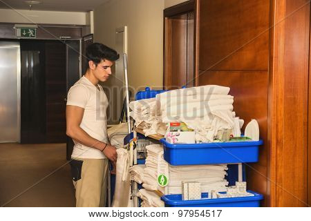 Young man pushing a housekeeping cart in a hotel