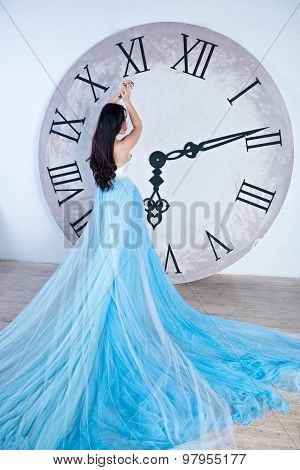 Beautiful Asian Girl In A Long Dress With Plume Standing Near The Huge Clock