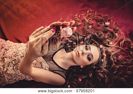 Girl Lying With Flowers On Hair. Charming Girl Showing A Rose.  Young Woman Has A Beautiful Face.