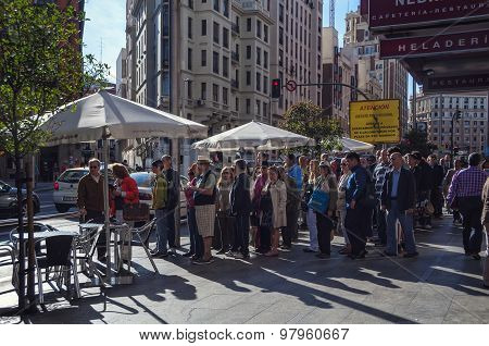 Unidentified people standing in the line at Gran Via in Madrid