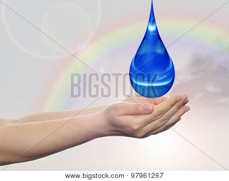 Concept or conceptual blue water or liquid drop falling in two woman hands on rainbow sky background