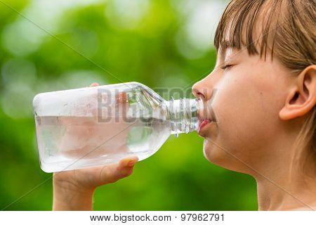 Girl Drinking Clean Tap Water From Transparent Glass Bottle