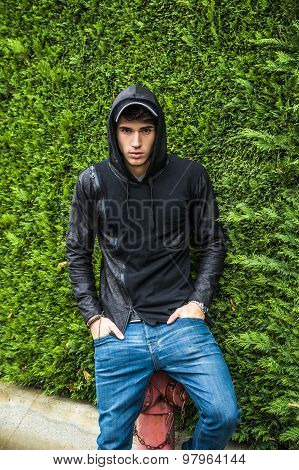 Handsome young man in black hoodie sweater standing outdoor