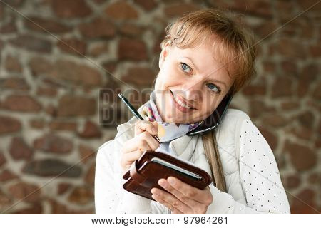 Girl Is Talking By Phone, Smiling And Writing Down