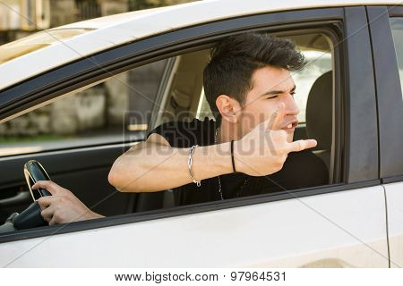 Young Man Driving a Car and showing the middle finger