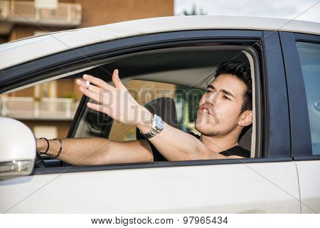 Angry Young Man Driving a Car and Yelling at Someone