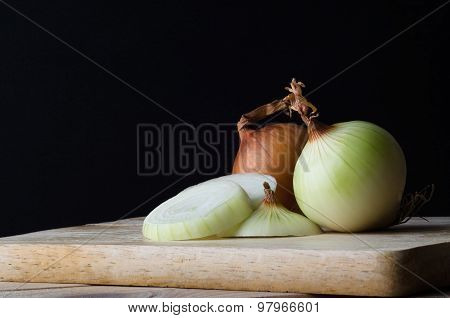 Whole And Sliced Onions On Chopping Board With Black Background
