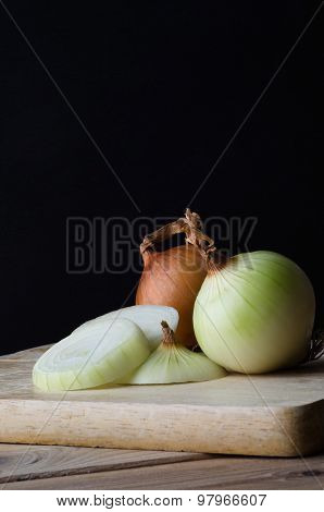 Whole And Sliced Onions On Chopping Board