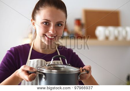 Youn woman holding pan in hands on kitchen