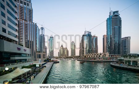 Dubai, United Arab Emirates - December 14, 2013: Panoramic view with modern skyscrapers and water channel of Dubai Marina in evening, United Arab Emirates