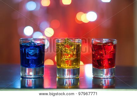 Three glasses with berry liqueur on the bar counter at a nightclub, magic light bokeh