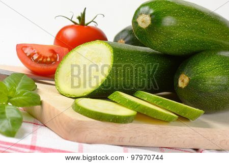 detail of fresh courgettes and tomatoes on wooden cutting board