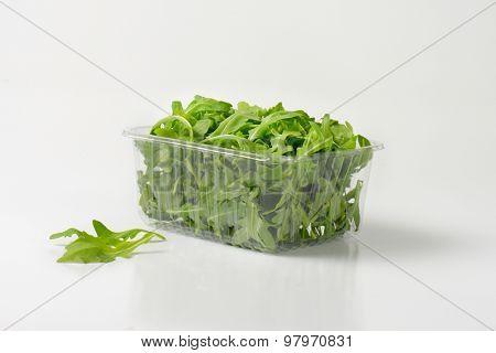 package of fresh arugula on white background