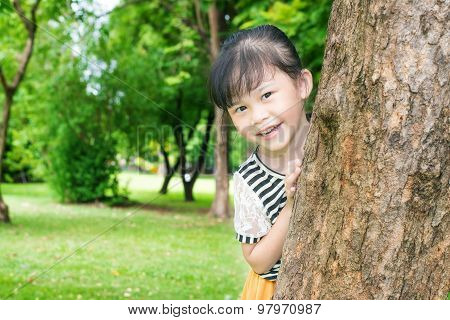 Asian Little Girl Smiling Behind A Tree In Park