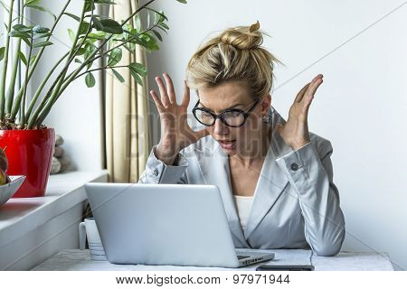 Business woman in a state of shock sitting near the computer.