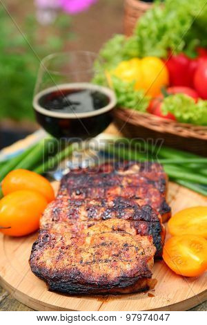 Grilled meat and vegetables on wooden table