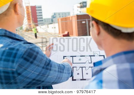 building, construction, development, teamwork and people concept - close up of builders with blueprint at building site