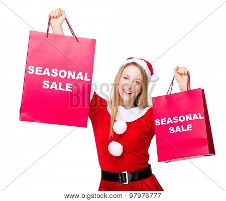 Woman with christmas party dress hold up with shopping bag and showing seasonal sale