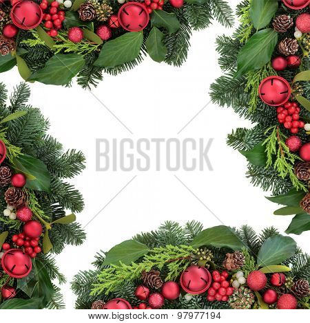 Christmas background border with red bell bauble decorations, holly, ivy, mistletoe, fir and winter greenery over white background.
