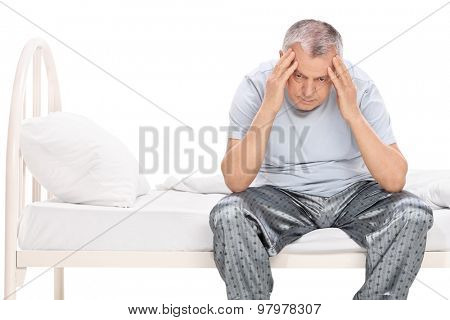 Frustrated senior sitting on a bed in his pajamas and looking down isolated on white background