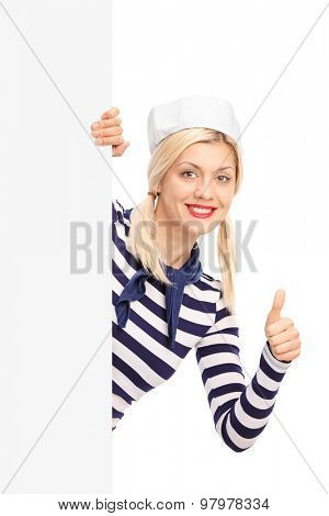 Vertical shot of a female sailor giving a thumb up and posing behind a blank billboard isolated on white background