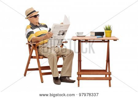 Senior gentleman sitting at a coffee table and reading a newspaper.The newspaper is custom made, text is Latin and the pictures are my copyright. Additionally property release uploaded.