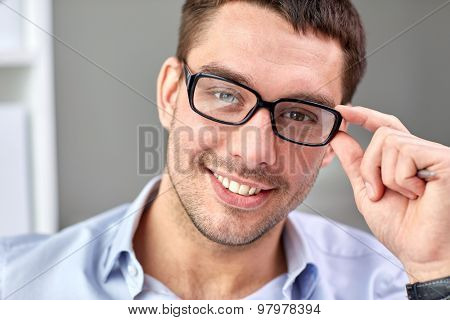 business, people and work concept - portrait of smiling businessman in eyeglasses face in office
