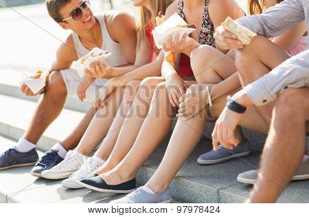 friendship, leisure, summer, fast food and people concept - group of happy friends eating hot dogs and sandwiches on city square