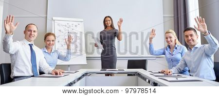 business, people and teamwork concept - group of smiling businesspeople meeting and waving hands in office