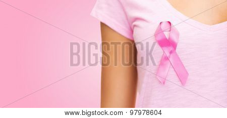 healthcare, people, charity and medicine concept - close up of woman in t-shirt with breast cancer awareness ribbon over pink background