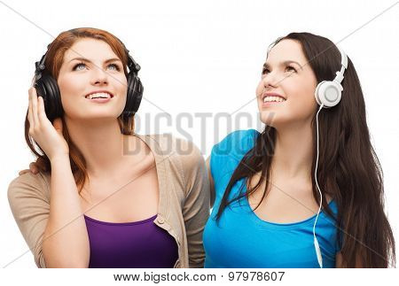 music and technology concept - two smiling teenagers with headphones looking up