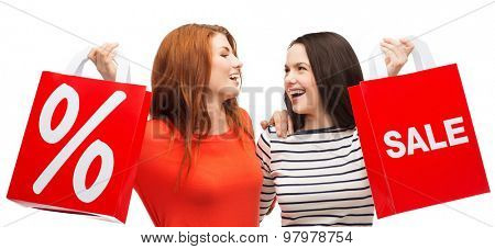 shopping, sale, and gift sconcept - two smiling teenage girls with shopping bags and percent sign