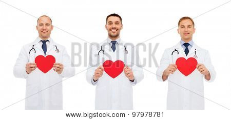 medicine, profession, cardiology, charity and health care concept - three smiling male doctors with red heart and stethoscope
