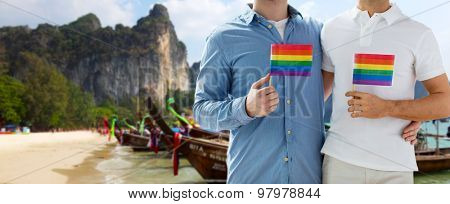 people, homosexuality, same-sex marriage, travel and love concept - close up of happy male gay couple holding rainbow flags and hugging over thailand beach background
