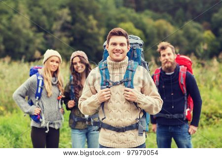 adventure, travel, tourism, hike and people concept - group of smiling friends standing with backpacks