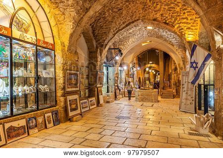 JERUSALEM, ISRAEL - JULY 16, 2015: Gift shops  gallery in ancient stone vault passage in Old City of Jerusalem - one of the oldest cities in the world and holy in Judaism, Islam and Christianity.