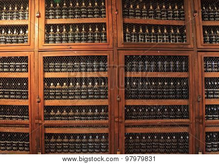 FUNCHAL, MADEIRA - OCTOBER 08, 2011: The shelves are made with sweet wine bottles Madera.  Long rows of shelves made of mahogany.  Museum - repository of expensive vintage wine Madera