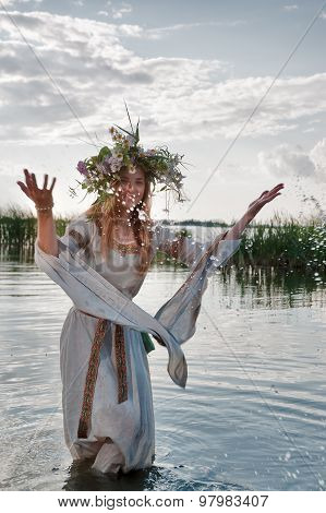 Beautiful woman with flower wreath in water