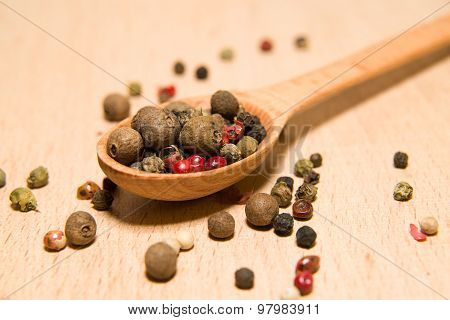 Spoon Filled With A Mixture Of Grains Of Pepper Are On A Wooden Surface