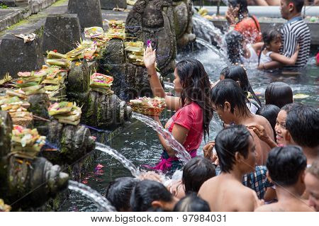 Balinese families come to the sacred springs water temple of Tirta Empul in Bali Indonesia
