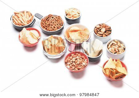 Salty crackers, tortilla chips and other savory snacks isolated on white background